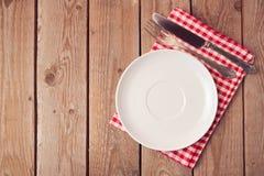 Κενό πιάτο με το μαχαίρι και δίκρανο στον ξύλινο αγροτικό πίνακα επάνω από την όψη στοκ εικόνα με δικαίωμα ελεύθερης χρήσης
