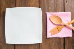 Κενό πιάτο, ξύλινα κουτάλι και δίκρανο στο ξύλινο υπόβαθρο Στοκ εικόνα με δικαίωμα ελεύθερης χρήσης