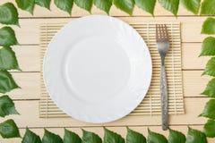 Κενό πιάτο σε ένα χαλί μπαμπού με ένα δίκρανο, άποψη από την κορυφή, σε ένα ξύλινο υπόβαθρο, που πλαισιώνεται με τα φύλλα ενός δέ Στοκ Εικόνα