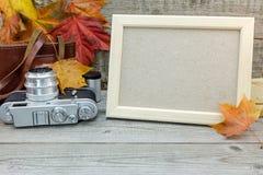 Κενό πλαίσιο φωτογραφιών, αναδρομική κάμερα στο παλαιό γκρίζο ξύλινο γραφείο με το vib Στοκ Εικόνα