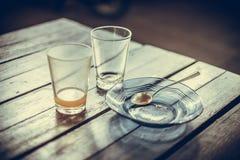 Κενό ποτήρι του καυτού τσαγιού μέσα με το πιατάκι και το κουτάλι στον ξύλινο πίνακα Στοκ Εικόνες