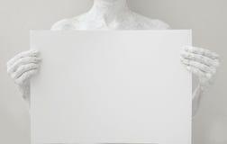 Κενό πρότυπο αφισών σχεδίου Γυναίκα που καλύπτεται με το άσπρο χρώμα που κρατά ένα έγγραφο Στοκ φωτογραφία με δικαίωμα ελεύθερης χρήσης