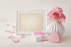 Κενό πλαίσιο φωτογραφιών, δώρο και ρομαντικά λουλούδια στοκ φωτογραφίες