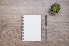 Κενό σε ένα άσπρο σημειωματάριο με τις εγκαταστάσεις σε ένα ξύλινο γραφείο Στοκ φωτογραφία με δικαίωμα ελεύθερης χρήσης