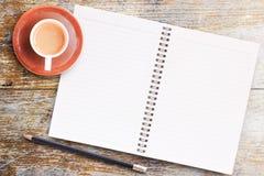 Κενό σημειωματάριο εγγράφου με το μολύβι και φλιτζάνι του καφέ στην ξύλινη ετικέττα στοκ εικόνες
