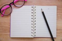 Κενό σημειωματάριο με ένα μολύβι και eyeglasses Στοκ Εικόνες