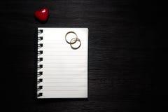 Κενό σημειωματάριο με τα δαχτυλίδια καρδιών και γάμου στο μαύρο υπόβαθρο στοκ εικόνες