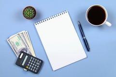Κενό σημειωματάριο με τη μάνδρα, τον καφέ, τα δολάρια, τον υπολογιστή και τον κάκτο σε ένα μπλε υπόβαθρο Αντιγράψτε το διάστημα Τ Στοκ Φωτογραφία