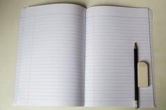 Κενό σημειωματάριο με το μολύβι και γόμα στον πίνακα Στοκ φωτογραφίες με δικαίωμα ελεύθερης χρήσης