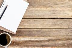 Κενό σημειωματάριο, μολύβι και καφές εγγράφου στην καφετιά ξύλινη επιτραπέζια ΤΣΕ στοκ φωτογραφίες