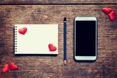 Κενό σημειωματάριο, μολύβι και κόκκινη καρδιά στον ξύλινο πίνακα με το τηλεφωνικό BL Στοκ εικόνες με δικαίωμα ελεύθερης χρήσης