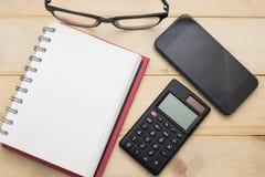 Κενό σημειωματάριο τοπ άποψης, υπολογιστής, γυαλιά και έξυπνο τηλέφωνο που τίθενται Στοκ Φωτογραφίες