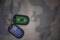κενό στρατού, ετικέττα σκυλιών με τη σημαία της Βραζιλίας και της Ουρουγουάης στο χακί υπόβαθρο σύστασης Στοκ φωτογραφίες με δικαίωμα ελεύθερης χρήσης