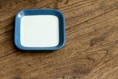 Κενό τετραγωνικό άσπρο και μπλε πιάτο χρώματος στο ξύλο Στοκ Εικόνες