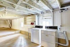 Κενό υπόγειο στο αμερικανικό σπίτι με το πλυντήριο Στοκ εικόνες με δικαίωμα ελεύθερης χρήσης