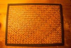 Κενό υφαμένο μπαμπού χαλί θέσεων στο ξύλινο επιτραπέζιο υπόβαθρο Στοκ φωτογραφίες με δικαίωμα ελεύθερης χρήσης