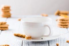 Κενό φλυτζάνι έτοιμο για το ζεστό ποτό με τα μπισκότα στον άσπρο αγροτικό πίνακα Στοκ εικόνα με δικαίωμα ελεύθερης χρήσης