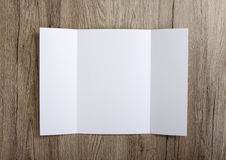 Κενό φυλλάδιο πτυχών πυλών στο ξύλινο υπόβαθρο για να αντικαταστήσει το de σας Στοκ Εικόνα