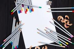 Κενό φύλλο των μολυβιών εγγράφου και χρώματος στο μαύρο ξύλινο backgroun Στοκ εικόνες με δικαίωμα ελεύθερης χρήσης