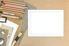Κενό φύλλο εγγράφου και διάφορα εργαλεία σχεδίων σε καφετί χαρτί τεχνών Στοκ Εικόνα