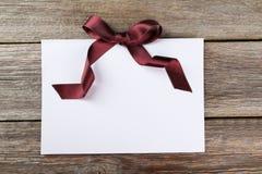 Κενό φύλλο εγγράφου με burgundy το τόξο στο ξύλινο υπόβαθρο Στοκ Εικόνες