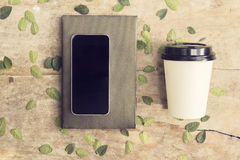 Κενό smartphone στο βιβλίο με το φλιτζάνι του καφέ για να πάει Στοκ Εικόνες