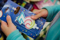 Κερί για το κέικ με τον αριθμό τρία στα χέρια του αγοραστή στοκ εικόνες