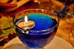 Κερί με τα επιπλέοντα σώματα πυρκαγιάς σε ένα σκάφος γυαλιού με το μπλε νερό Επιτραπέζιο ντεκόρ του νέου έτους στοκ φωτογραφία με δικαίωμα ελεύθερης χρήσης