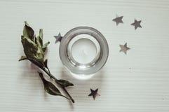 Κερί που στέκεται σε μια άσπρη ξύλινη κορυφή υποβάθρου στοκ εικόνες