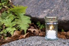 Κερί που στέκεται στην ταφόπετρα και το κάψιμο Στοκ Φωτογραφίες