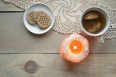 Κερί του ρόδινου άλατος με την πυρκαγιά, ένα φλυτζάνι compote μήλων και πιάτο με τα μπισκότα Στοκ φωτογραφία με δικαίωμα ελεύθερης χρήσης