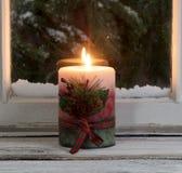 Κερί Χριστουγέννων που καίγεται στη στρωματοειδή φλέβα παραθύρων με το χιονώδη αειθαλή στηθόδεσμο στοκ εικόνα