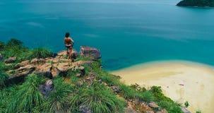 Κεραία: Ένα κορίτσι στέκεται πάνω από ένα βουνό και εξετάζει κάτω την παραλία απόθεμα βίντεο
