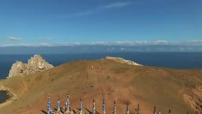 Κεραία πέρα από τις ιερές ξύλινες στήλες σαμάνων με τις ζωηρόχρωμες κορδέλλες κοντά στο βράχο Shamanka, νησί Olkhon, Baikal λίμνη φιλμ μικρού μήκους