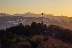 Κεραία, ραδιο πύργος στο υπόβαθρο του όμορφου ηλιοβασιλέματος βραδιού στα καυκάσια βουνά με τις αιχμές χιονιού, Arkhyz, Ρωσία Στοκ εικόνα με δικαίωμα ελεύθερης χρήσης