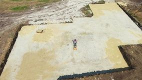 Κεραία της επιφάνειας άμμου βύθισης εργαζομένων με το δονητικό συμπιεστή πιάτων στο κοίλωμα απόθεμα βίντεο