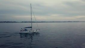 Κεραία Pan+follow 4k της πλέοντας βάρκας στο ηλιοβασίλεμα cloudscape απόθεμα βίντεο