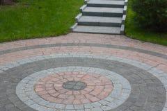 Κεραμίδια γρανίτη που σχεδιάζονται υπό μορφή κύκλου με μια έξοδο μέσω των βημάτων Άλλος που σημαίνει: όταν περπατάτε γύρω σε έναν Στοκ Εικόνες