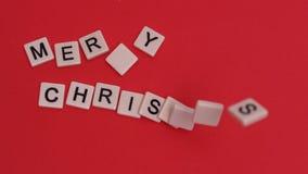 Κεραμίδια επιστολών που κινούνται για να εξηγήσει τη Χαρούμενα Χριστούγεννα στο κόκκινο υπόβαθρο απόθεμα βίντεο
