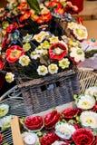 Κεραμικά διακοσμητικά λουλούδια στο ψάθινο καλάθι Στοκ Φωτογραφίες