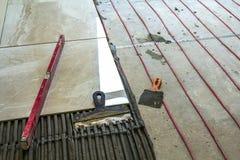 Κεραμικά κεραμίδια και εργαλεία για tiler Εγκατάσταση κεραμιδιών πατωμάτων Εγχώρια βελτίωση, ανακαίνιση - κόλλα πατωμάτων κεραμικ Στοκ εικόνες με δικαίωμα ελεύθερης χρήσης