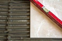 Κεραμικά κεραμίδια και εργαλεία για tiler Εγκατάσταση κεραμιδιών πατωμάτων Εγχώρια βελτίωση, ανακαίνιση - κόλλα πατωμάτων κεραμικ Στοκ Εικόνα