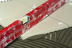 Κεραμικά κεραμίδια και εργαλεία για tiler Εγκατάσταση κεραμιδιών πατωμάτων Εγχώρια βελτίωση, ανακαίνιση - κόλλα πατωμάτων κεραμικ Στοκ Φωτογραφία