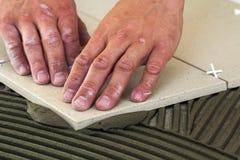 Κεραμικά κεραμίδια και εργαλεία για tiler Χέρι εργαζομένων που εγκαθιστά τα κεραμίδια πατωμάτων Εγχώρια βελτίωση, ανακαίνιση - κό Στοκ Εικόνα
