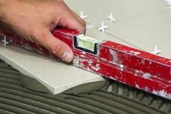 Κεραμικά κεραμίδια και εργαλεία για tiler Χέρι εργαζομένων που εγκαθιστά τα κεραμίδια πατωμάτων Εγχώρια βελτίωση, ανακαίνιση - κό στοκ εικόνες