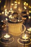 Κεραμικά μοντέρνα φλυτζάνια στα πουλόβερ και αναδρομική γιρλάντα Χριστουγέννων στο υπόβαθρο φω'των bokeh πεδίο βάθους ρηχό Βαμμέν Στοκ εικόνες με δικαίωμα ελεύθερης χρήσης
