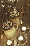 Κεραμικά μοντέρνα φλυτζάνια στα πουλόβερ και αναδρομική γιρλάντα Χριστουγέννων στο υπόβαθρο φω'των bokeh πεδίο βάθους ρηχό Βαμμέν Στοκ Εικόνα