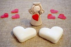 Κεραμικός άγγελος με τις καρδιές άνδρας αγάπης φιλιών έννοιας στη γυναίκα Στοκ εικόνες με δικαίωμα ελεύθερης χρήσης