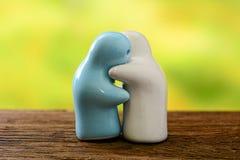 Κεραμικό αγκάλιασμα συναισθήματος κουκλών στο ξύλινο και υπόβαθρο φύσης Στοκ φωτογραφία με δικαίωμα ελεύθερης χρήσης