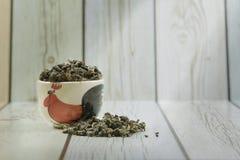 Κεραμικό κύπελλο με τα κινεζικά ξηρά πράσινα φύλλα τσαγιού oolong Στοκ Εικόνες